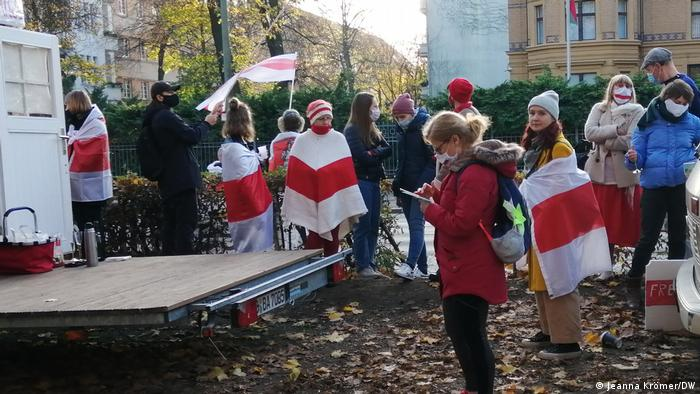 Peopel at alternative 'embassy' of Belarus, draped in red and white flags