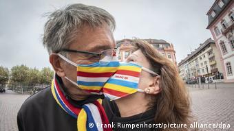 Mann und Frau mit Masken vor dem Gesicht küssen sich.