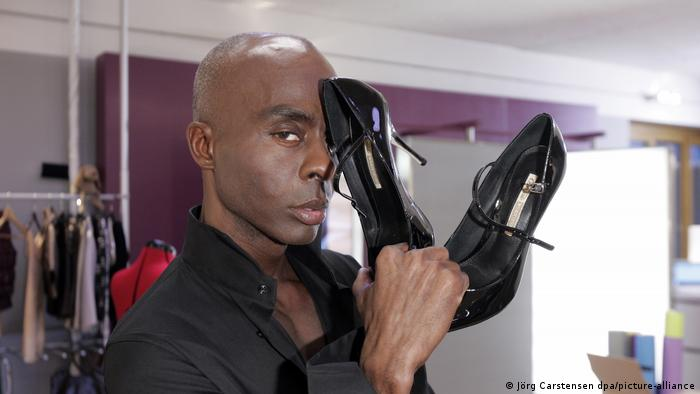 Bruce Darnell holding up a pair of black high heels (Jörg Carstensen dpa/picture-alliance)
