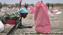 FILE - In this Wednesday, May 2, 2018 file photo, a woman scoops fallen sorghum grain off the ground after an aerial food drop by the World Food Program (WFP) in the town of Kandak, South Sudan. The World Food Program on Friday, Oct. 9, 2020 won the 2020 Nobel Peace Prize for its efforts to combat hunger and food insecurity around the globe. (AP Photo/Sam Mednick, File) |