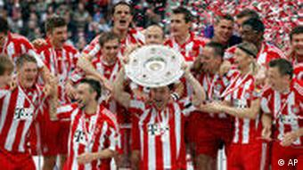 Munich's Mark van Bommel , center with trophy, and the other players of Bayern Munich celebrate after becoming the new Bundesliga champion after the German first division Bundesliga soccer match between Hertha BSC Berlin and Bayern Munich in Berlin, Germany, Saturday, May 8, 2010.