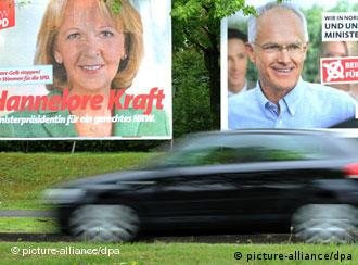 A biker passes two election signs for the SPD and the CDU