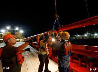Arbeiter auf einem Versorgungschiff am Unglücksort ziehen den Haken eines Krans an Bord (Foto: AP)