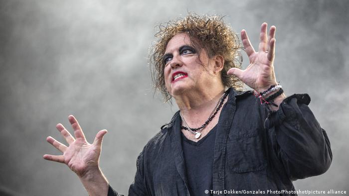 Robert Smith steht mit dunkel geschminkten Augen, lackierten Fingernägeln und toupierten Haaren auf der Bühne und hebt beschwörend die Hände (Terje Dokken/Gonzales Photo/Photoshot/picture alliance)