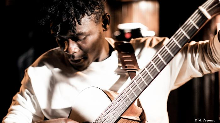 Melchi Vepouyoum wearing white, with a guitar (M. Veyououm)