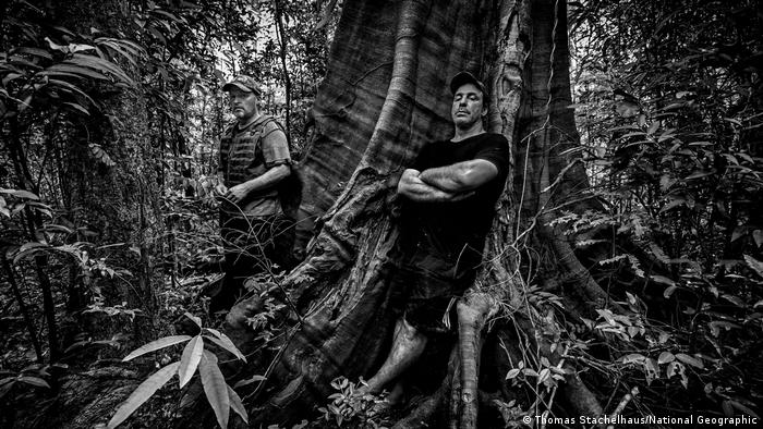 Joey Kelly and Till Lindemann pose next to a large tree in a black and white photo