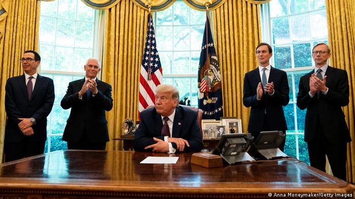Donald Trump in the Oval Office surrounded by men