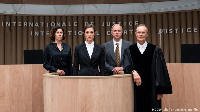 Film still from Ökozid showing people in a courtroom