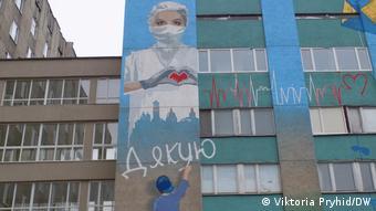 Стена больницы скорой помощи в Киеве с граффити: врач в маске и мальчик, который пишет слово Спасибо