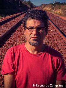 Cineasta Renato Barbieri diante de trilhos de trem