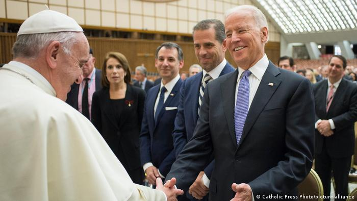 Pope Francis and Joe Biden smiling and shaking hands after an audience in 206