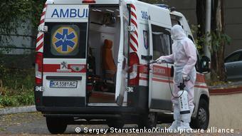 Санитар дезинфицирует машину скорой помощи в Киеве