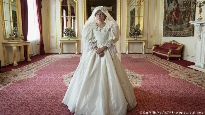 Emma Corrin als Prinzessin Diana in The Crown steht im Hochzeitskleid in einem Zimemr des Palasts