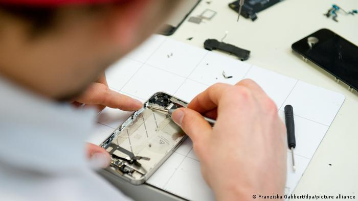 A picture showing a man repairing a smartphone