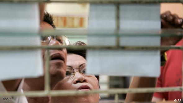 Voters check their names outside a voting precinct in San Juan