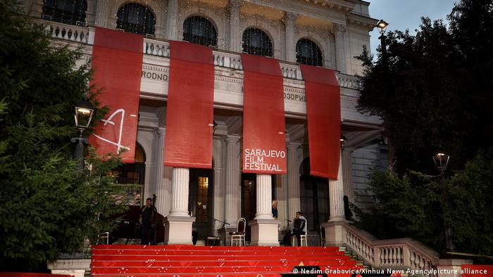 Das Gebäude des Nationalen Theaters in Sarajevo. Aus dem Balkon hängen rote Flaggen mit der Aufschrift Sarajevo Film Festival (Nedim Grabovica/Xinhua News Agency/picture alliance )
