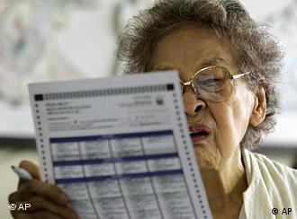 An elderly woman reviews her ballot at a voting center in San Juan, east of Manila