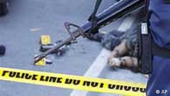 A policeman secures the crime scene in Bacoor town, where a Marine and a congressional candidate's bodyguard were killed in a clash