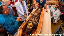 A picture taken on October 3, 2020 shows Egyptian Minister of Tourism and Antiquities Khaled Al-Anani (R), and Mustafa Waziri (L), Secretary General of the Supreme Council of Antiquities, unveil the mummy inside a sarcophagus excavated by the Egyptian archaeological mission working at the Saqqara necropolis, 30 kms south of the capital Cairo, which resulted in the discovery of a deep burial well with more than 59 human coffins closed for more than 2,500 years. - They were unearthed south of Cairo in the sprawling burial ground of Saqqara, the necropolis of the ancient Egyptian capital of Memphis, a UNESCO World Heritage site. Their exteriors are covered in intricate designs in vibrant colours as well as hieroglyphic pictorials. (Photo by Khaled DESOUKI / AFP) (Photo by KHALED DESOUKI/AFP via Getty Images)