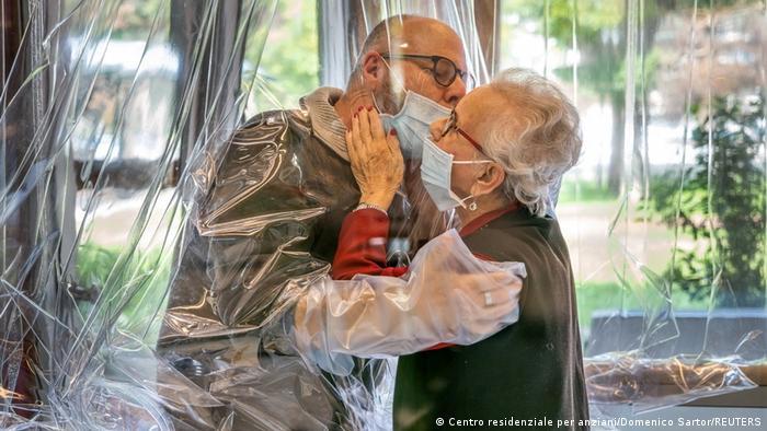 Пожилая женщина, живущая в доме престарелых, обнимается с пришедшим навестить ее сыном через пластиковую штору.