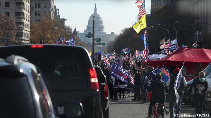 Manifestantes carregando bandeiras americanas, com a Casa Branca ao fundo