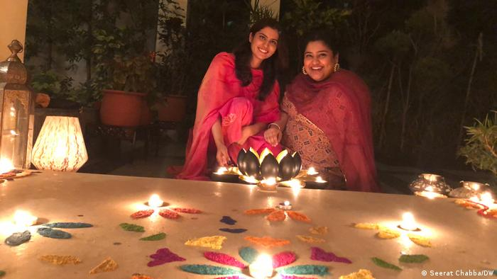 Two young women pose with their rangoli, a sacred pattern drawn on floors during auspicious occasions like Diwali (Seerat Chabba/DW)