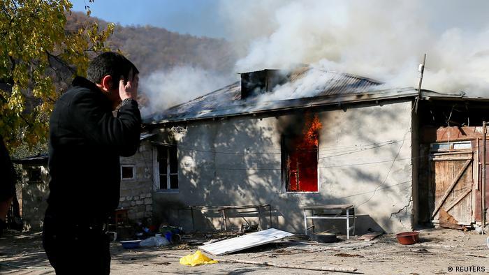 Жители Нагорного Карабаха покидают территории, перешедшие под контроль Азербайджана. Мужчина плачет у дверей горящего дома