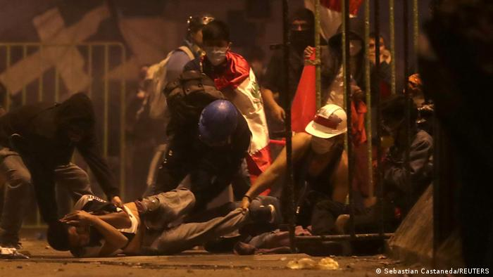 A protester lies injured on the ground