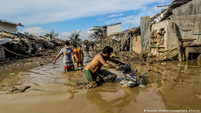 Residents wade through knee deep mud