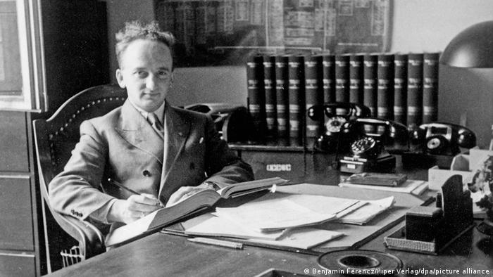 A picture of Ferencz in his 20s during the Nuremberg trials sitting at a desk with a book in his hand | Ben Ferencz