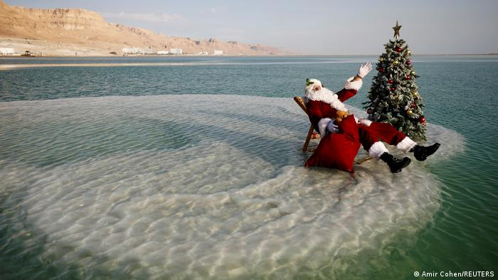Person dressed up as Santa Claus sitting in a deck chair beside a Christmas tree in the surf