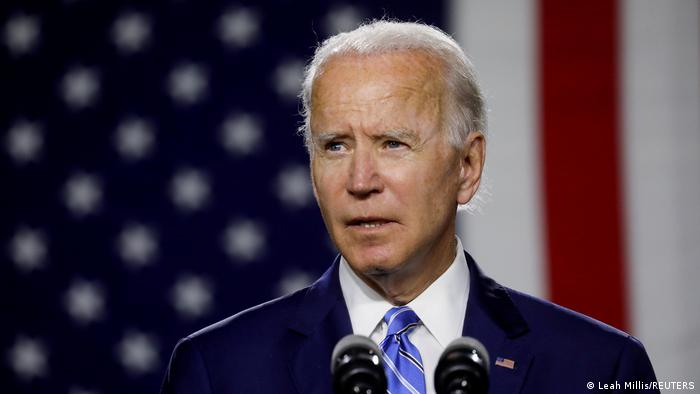 A photo of Joe Biden in front of an American flag