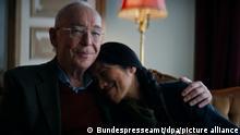 Ein betagter Mann hält eine asiatische Frau im Arm. Ein Filmstill der Corona-Kampagne der Bundesregierung