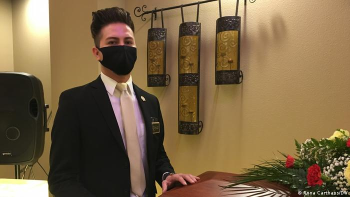 Jorge Ortiz in a dark suit and face mask at one of his funeral homes