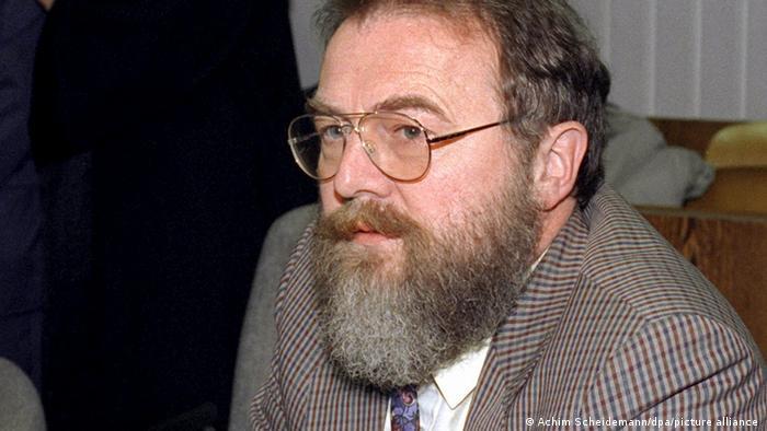 Homem de óculos, barba semigrisalha e paletó xadrez com camisa branca e gravata colorida