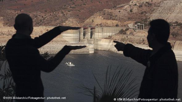 Two men stand in front of a dam in Jordan that is nearly empty