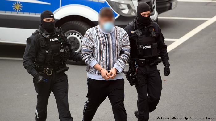 Zwei Polizisten führen ein Mann in Handschellen ab