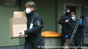 Polizisten tragen Pappkartons und Stative über einen Hof