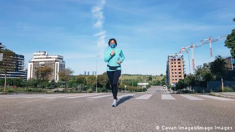 Woman wearing a mask and jogging through a city