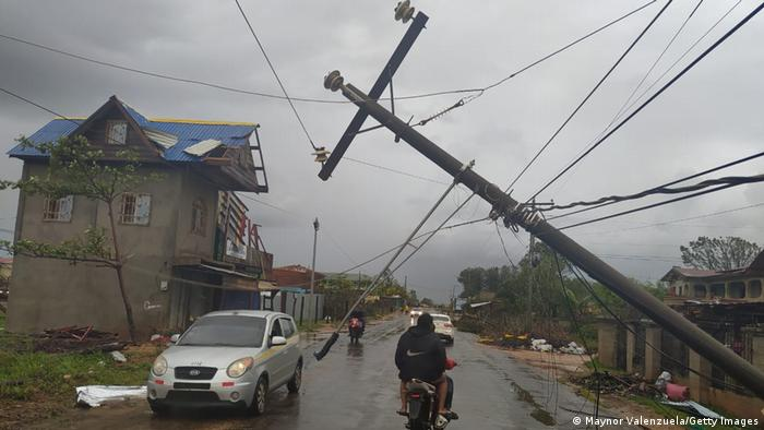 Traffic moving on a road with visible storm damage, including power lines barely standing after heavy winds, in Barrio El Aeropuerto on November 17, 2020 in Puerto Cabezas, Nicaragua. (Maynor Valenzuela/Getty Images)