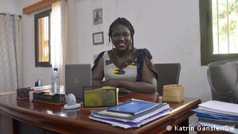 Sandrine Nama sits at her desk in front of her laptop