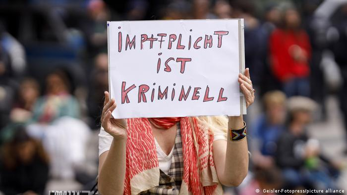 Woman in a crowd, holding a handwritten sign in front of her face stating that compulsory vaccination is a crime (in German)