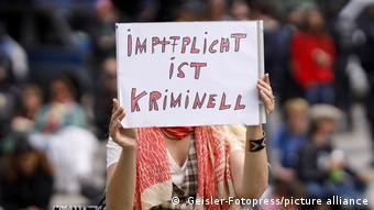 Обязательная вакцинация - это преступление, написано на плакате участницы протеста против принудительных прививок
