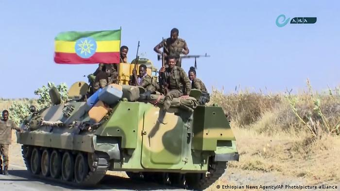This image made from undated video released by the state-owned Ethiopian News Agency on Monday, Nov. 16, 2020 shows Ethiopian military sitting on an armored personnel carrier next to a national flag