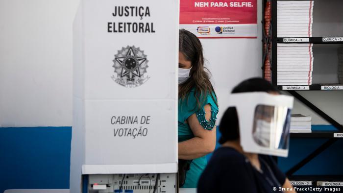 Mulher de máscara votando