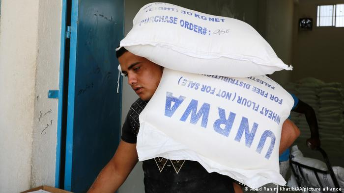 A Palestinian carries UNWRA aid sacks on his shoulder