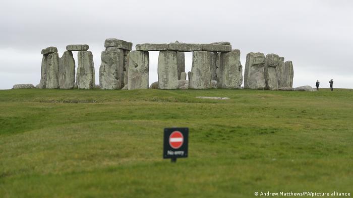 Riesige, rechteckige, aufgebauten Steine stehen auf einer grünen Wiese. Davor ist in Unschärfe ein rotes Verbotsschild mit der Aufschrift No entry zu sehen.