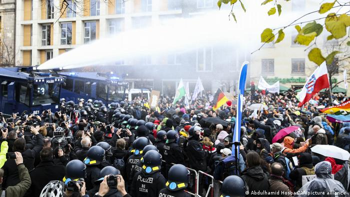 Police officers face off against thousands of demonstrators with water cannon as they gather near German parliament