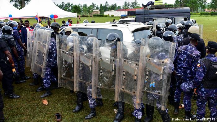 Ugandan riot police line up holding shields
