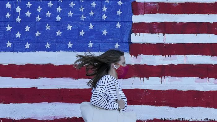 Девушка в защитной маске на фоне флага США